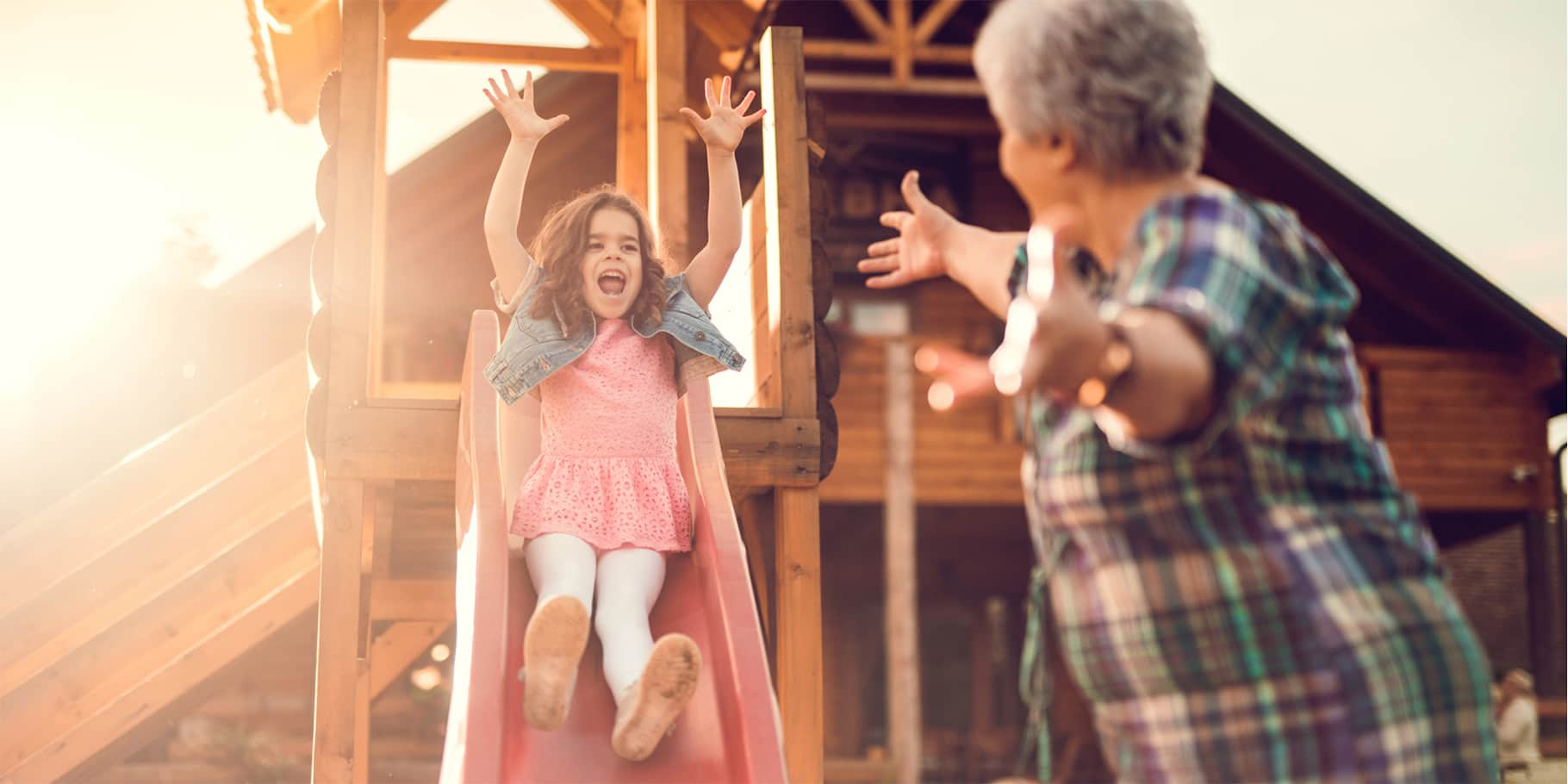 A young girl going down a slide with arms raised high and a grandmother at the bottom waiting to catch her.
