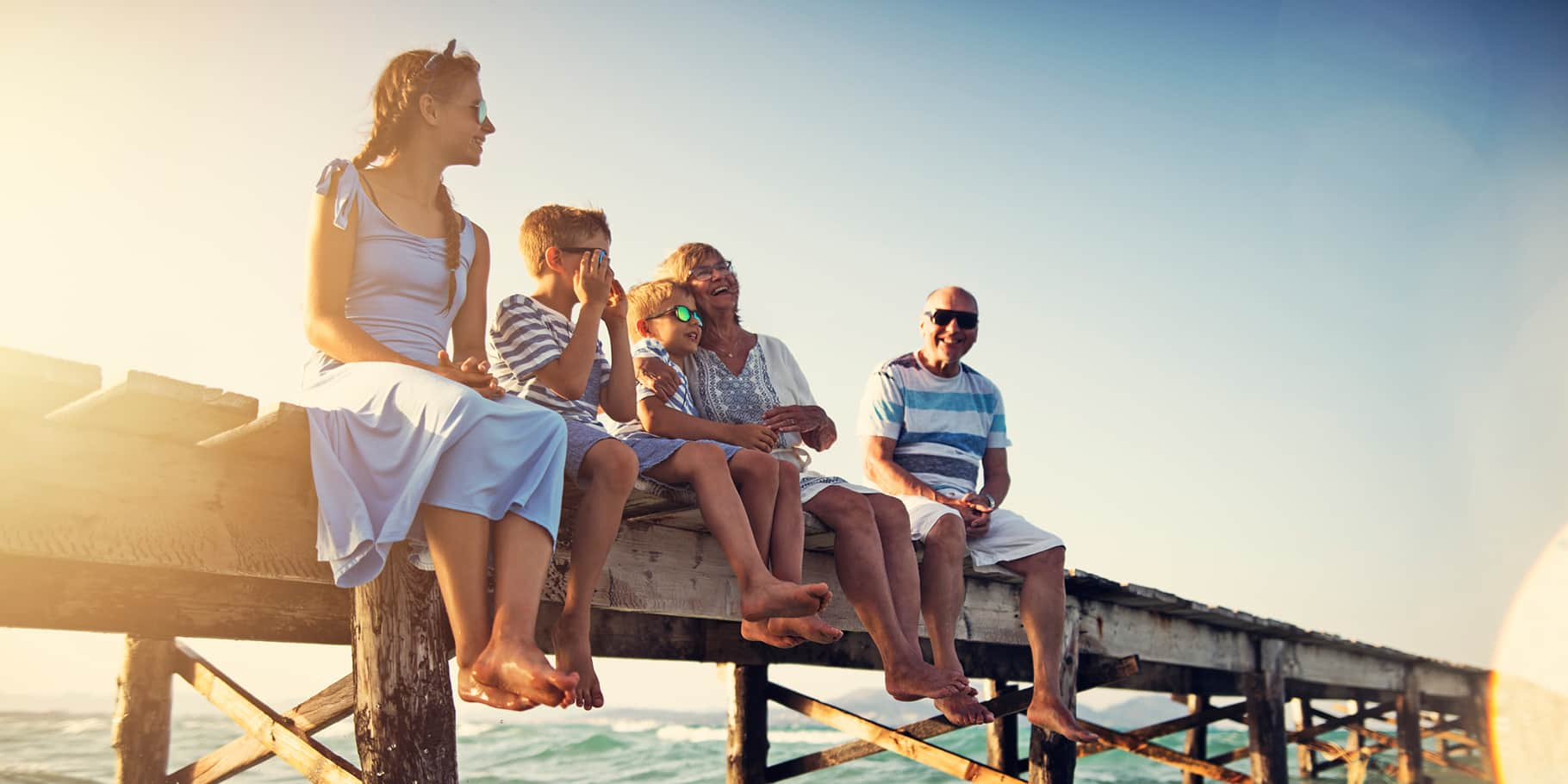 A family of 5 sitting on a pier on a sunny day with their feet hanging over the water.