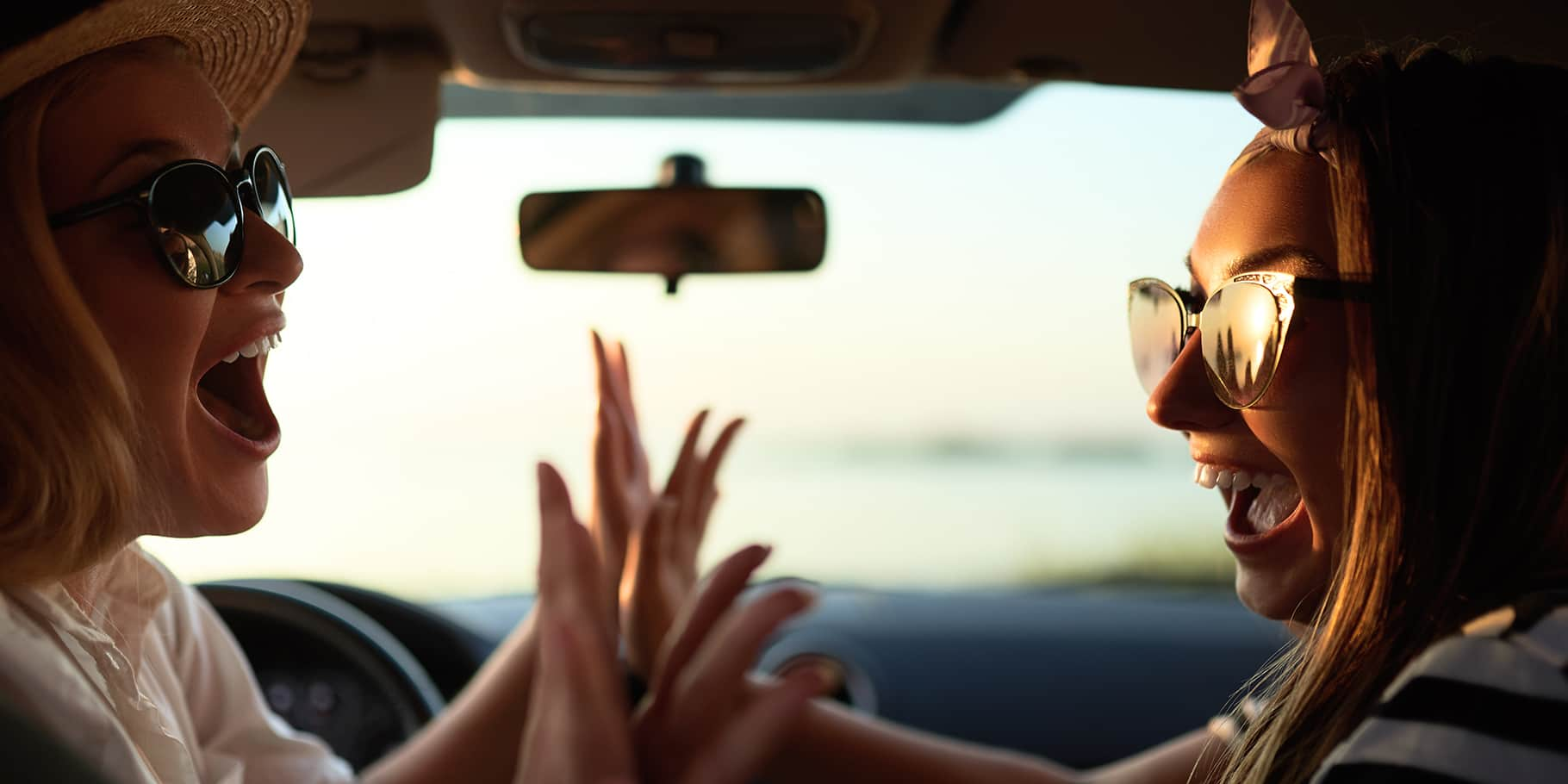 Two women giving eachother high-fives inside a car.