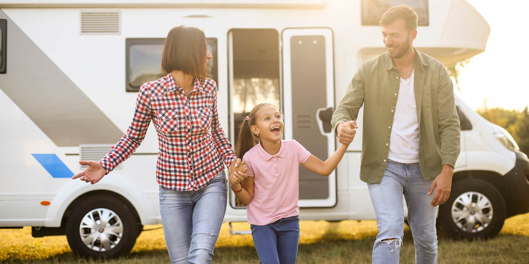 A young family holding hands in front of their RV.