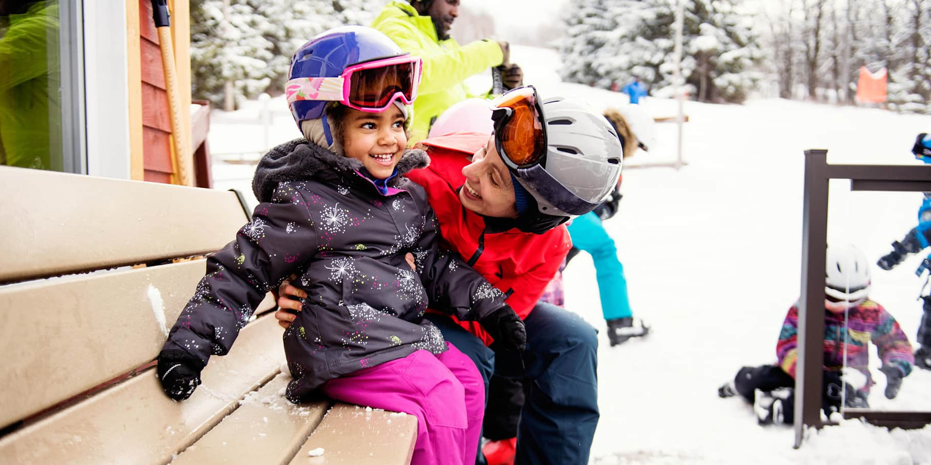 A mother helping her young daughter approach a ski lift.