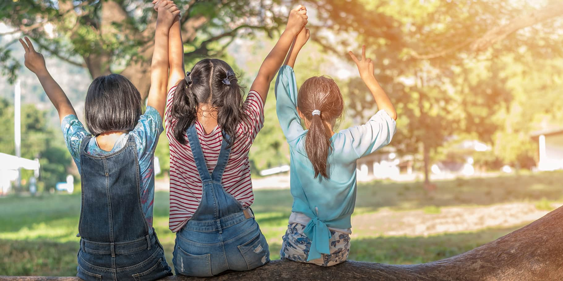 Three young girls sitting on a tree and making the peace sign with outstretched arms.